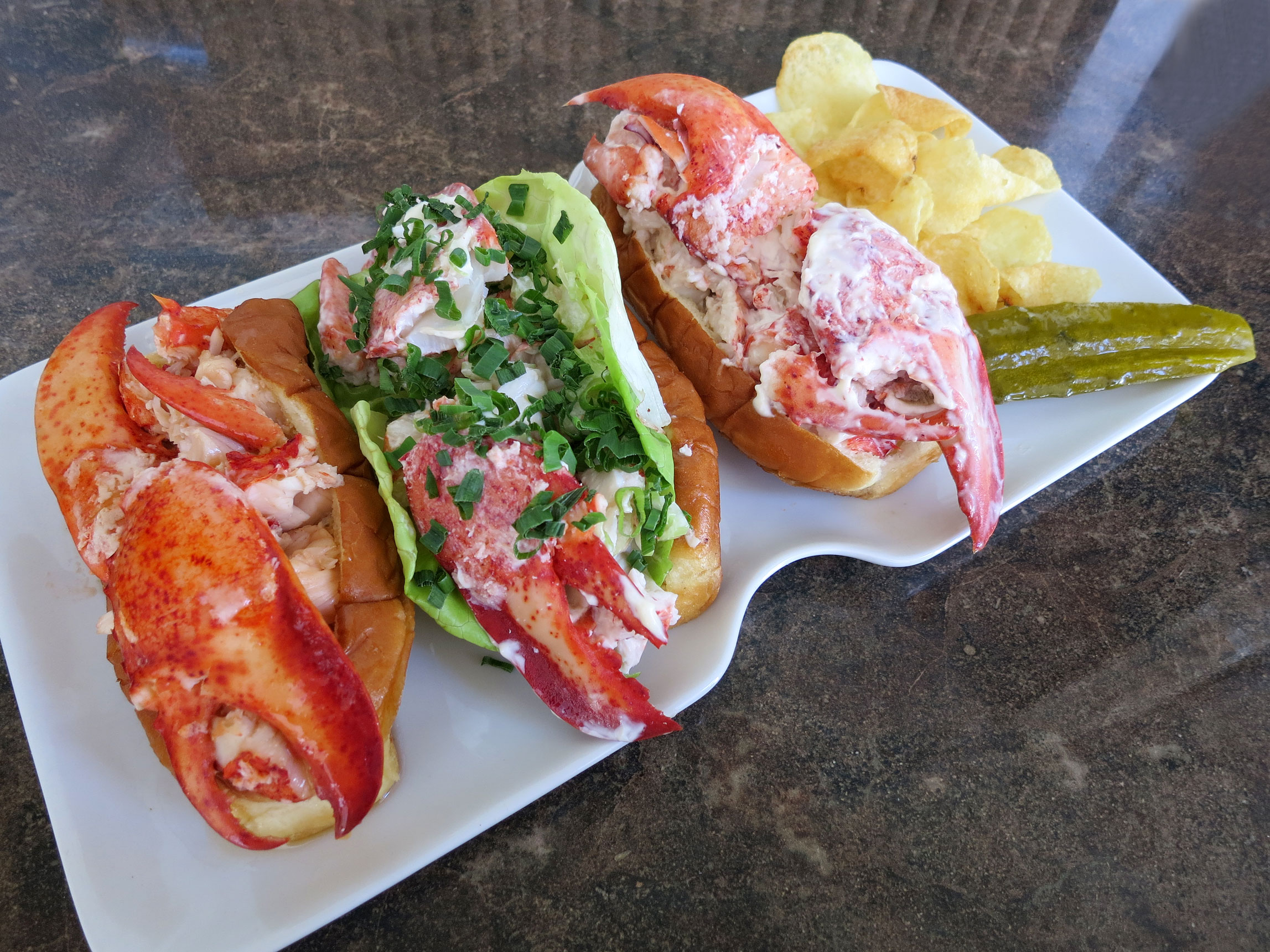 lobster rolls connecticut new england and maine style pomai s per ken lobster rolls left to right connecticut style new england style and maine style served maui style potato chips and dill pickle